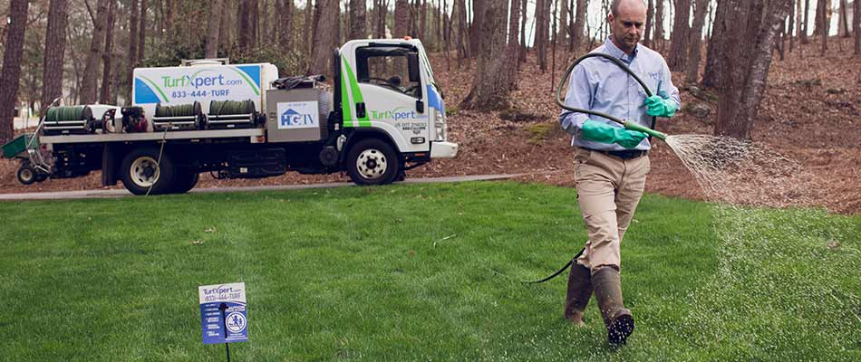 TurfXpert lawn care expert fertilizing a home lawn in Roswell, GA.